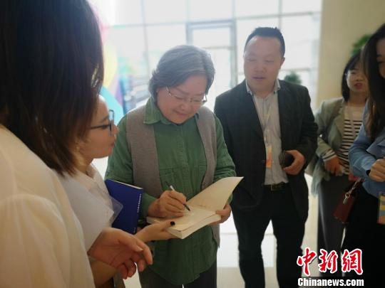 """知名绘本作家、""""好外婆""""蔡皋(中)为家长粉丝签名。 刘曼 摄"""